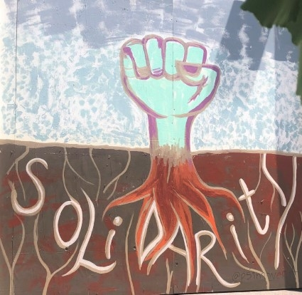 Solidarity - written below a fist, growing out of the ground with roots.