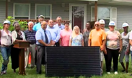 People gather in front of a solar panel in Marion, IL to mark the completion of the first training program under Future Energy Jobs Act.