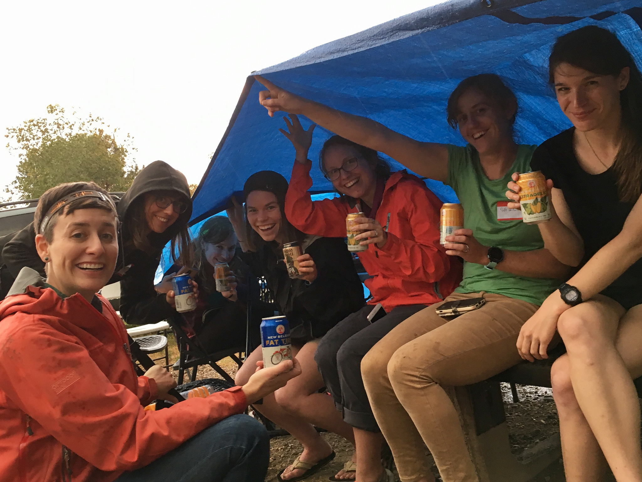 Several women sit under a large blue tarp, other women are wearing rain coats, smiling at the camera