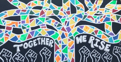 "A mural in Oakland has a colorful tree and says ""Together we rise"""